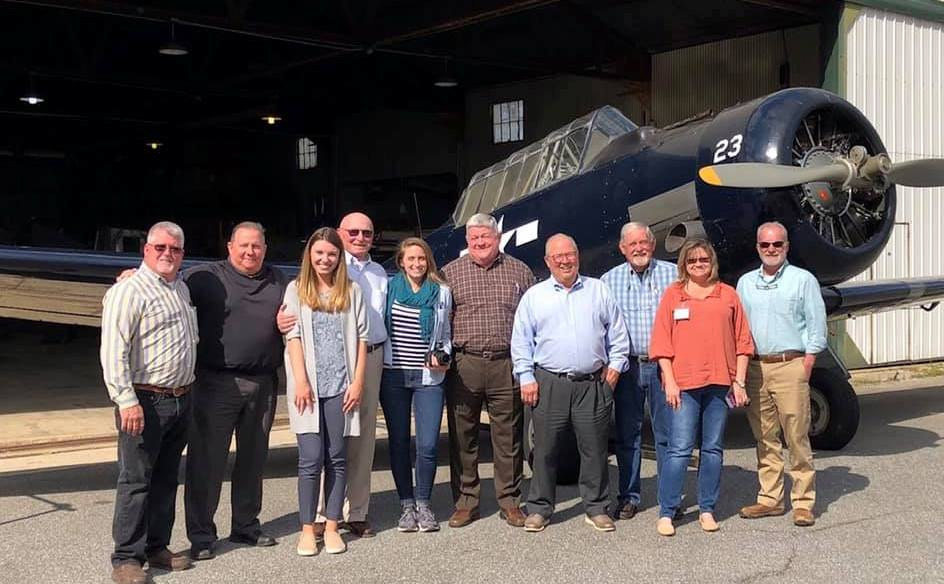 Group standing in front of old airplane