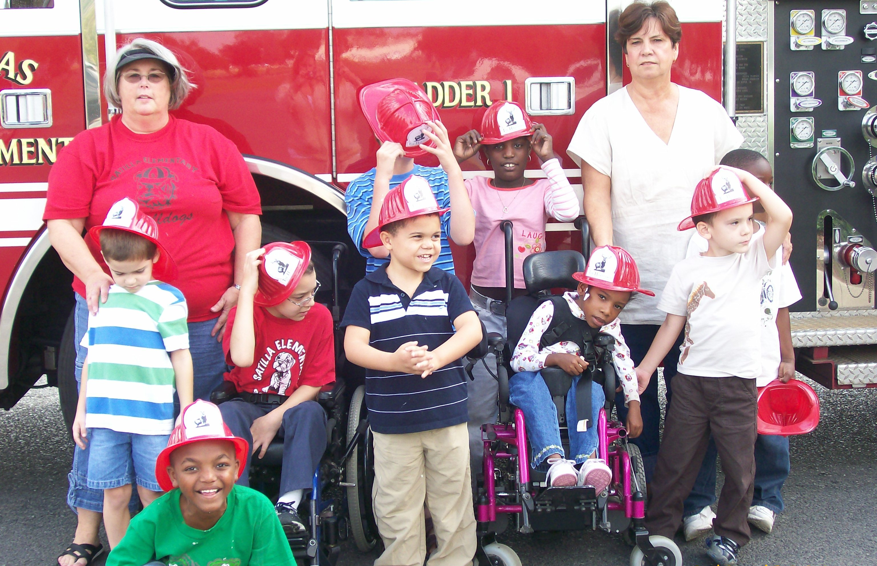 Children and chaperones stand next to fire truck