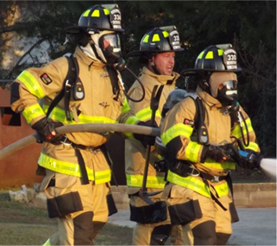 Fire fighters in gear running with water hose